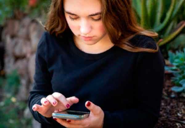 Девочка смотрит на экран своего телефона