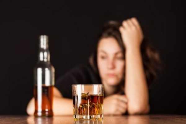 Замученная женщина, перед ней стоит бутылка и стакан со спиртным