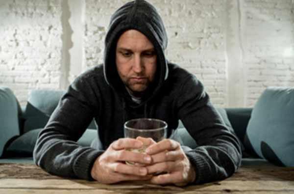 Мужчина в капюшоне сидит за столом, держит в руках стакан со спиртным