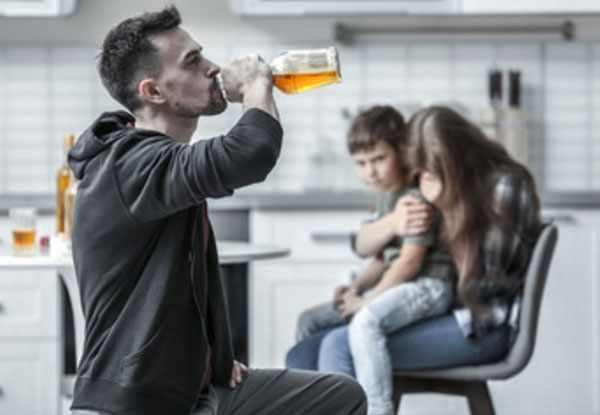 Мужчина бьет с бутылки. На заднем фоне его жена с ребенком на руках