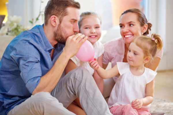 Папа надувает шарик, рядом дочки и жена