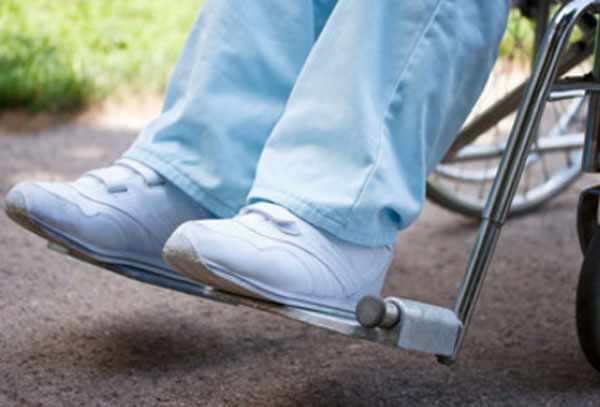 Ноги человека, сидящего на инвалидной коляске