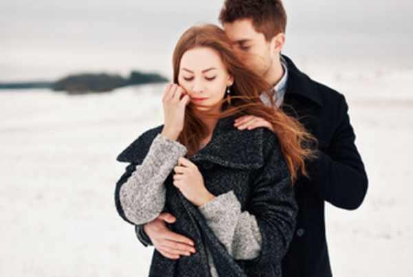 Мужчина стоит за девушкой, обнимает ее